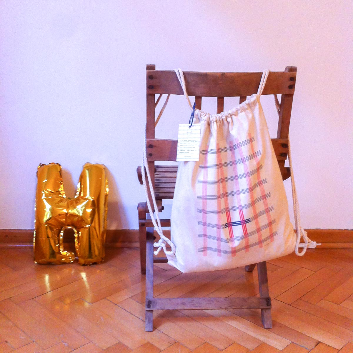 """Ekose"" backpack hanging on the back of a chair"