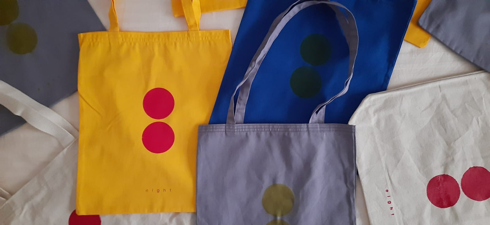 Eight totebags of a variety of colors are spread around overlapping one another.