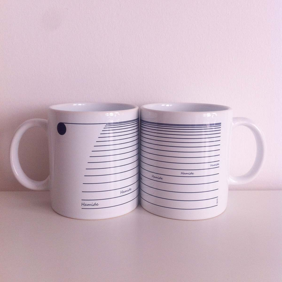 Two pieces of 7th year coffee mugs facing each other