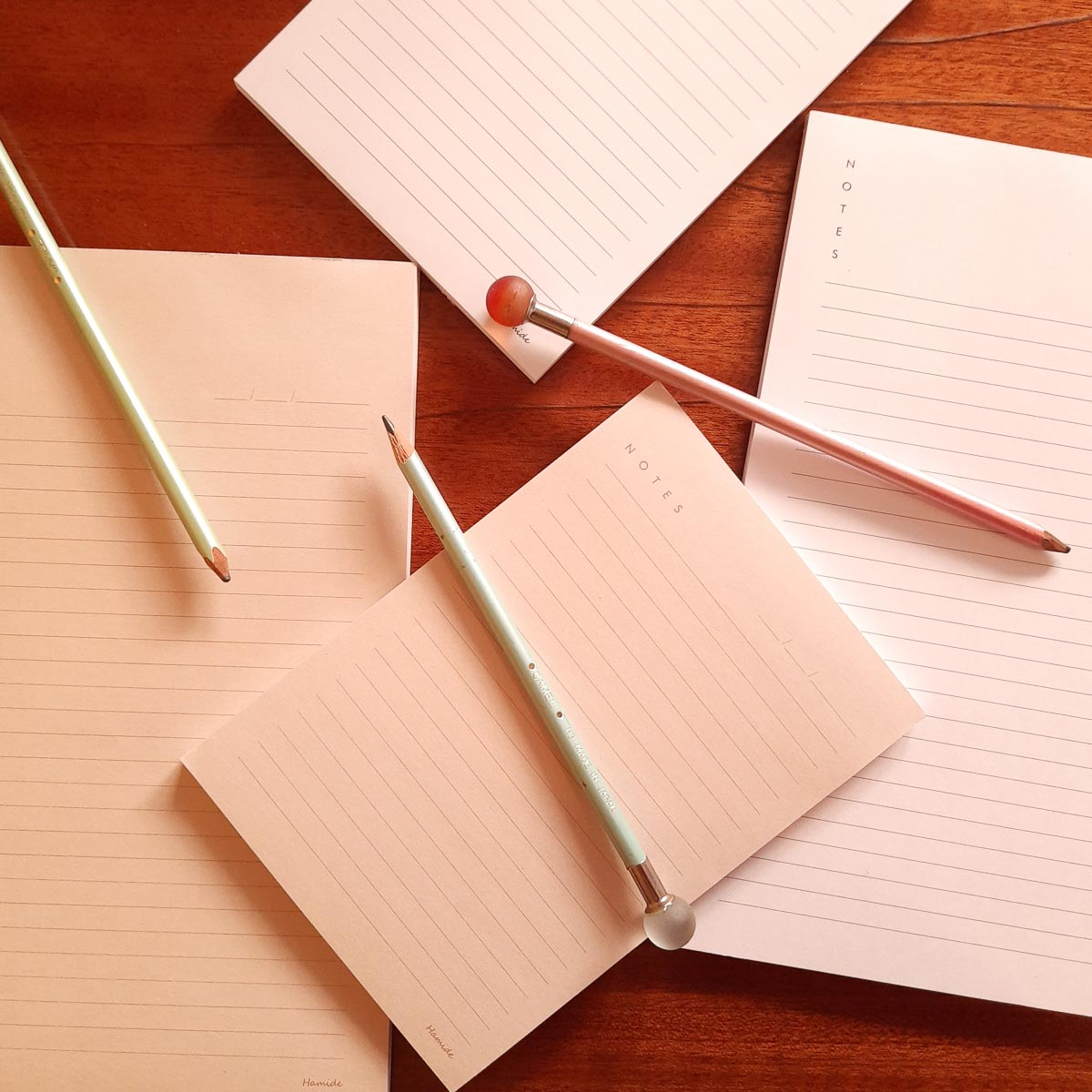 Hamide Basics notepads laying on a table with pencils
